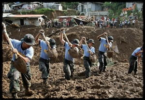 Oct 11: Filipino police dig for bodies in La Trinidad, Philippines, after Typhoon Parma.
