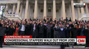 "Staffers raise their hands, gesturing ""Hands Up, Don't Shoot."""