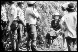 Police flank Dorothy Day, seated at a farm workers picket line in Lamont, California, in 1973.