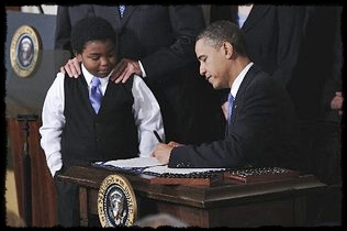 President Barack Obama signs the healthcare reform bill Tuesday in the White House as 11-year-old Marcellus Owens looks on. CHARLES DHARAPAK / AP