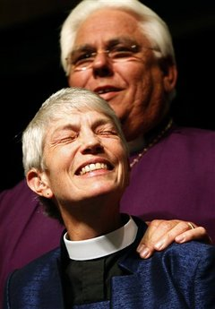 Mary Glasspool reacts during her election with Bishop Jon Bruno behind her.